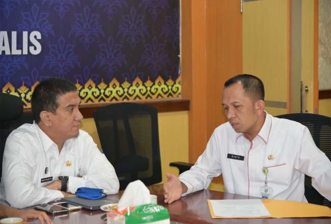 Kepala Bappeda Bengkalis (kiri) Hadi Prasetyos sedang berbincang-bincang dengan Sekretaris Bappeda Rinto.