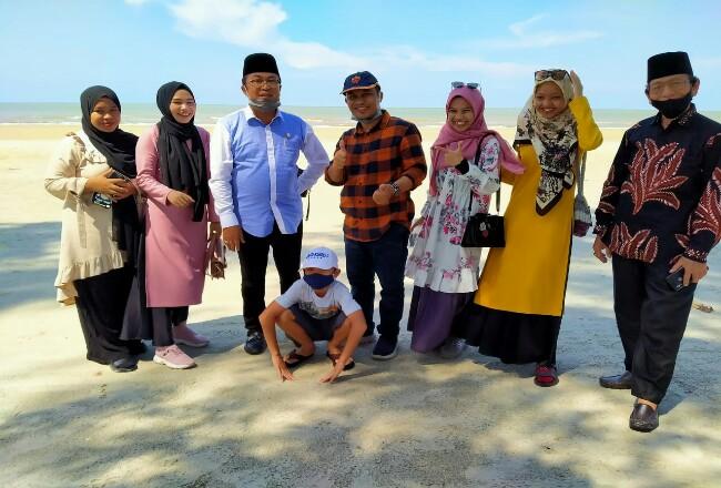 Sunaryo, Bagus Santoso, Kades Jamil, Sekdes Iwan Santoso, Setia Irawan, Kusnan dan wisatawan lokal menikmati pantai molek Ketapang.