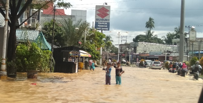 Anak-anak bermain di genangan banjir, kawasan Jalan Tuanku Tambusai Desa Babussalam, Rambah, akibat meluapnya Sungai Batang Lubuh. Ratusan rumah penduduk ikut terendam banjir