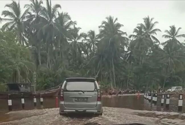 Salah satu mobil yang nekat menerjang genangan air pasang laut di jalan ruas Pematang Duku.