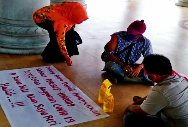 Dua warga gelar aksi diam sambil pajang poster dan bawa minyak goreng, di depan kantor Bupati Rohul, sebagai bentuk protes karena dianggap tidak terbukanya pengelolaan anggaran penanganan COVID-19 di Rohul.
