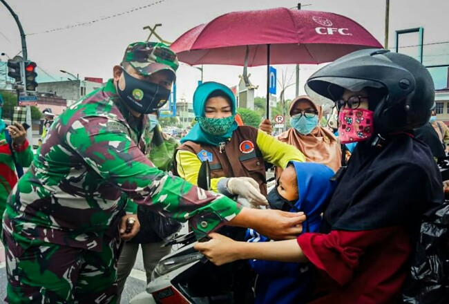 Dandim Dumai Letkol inf Irdhan bersama Ketua TP PKK Dumai Hj. Haslinar membagi-bagikan masker kepada masyarakat, baru-baru ini.
