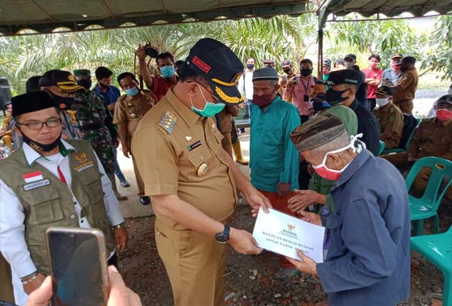 Bupati Rokan Hilir menyerahkan bantuan bedah rumah untuk masyarakat Kecamatan Pekaitan.
