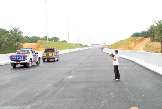 Seorang pegawai pemprov sedang melakukan pengecekan jalan tol Pekanbaru-Dumai. Jalan tol ini akan mengurai kepadatan arus kendaraan yang menghubungkan Pekanbaru-Dumai. FOTO: Gatra