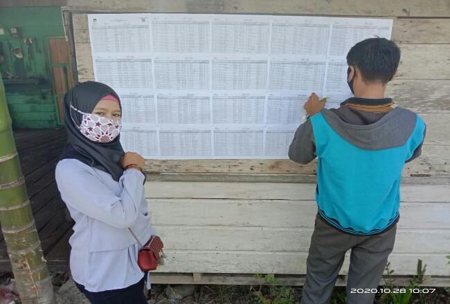 Petugas PPS menempel hasil DPT yang diumumkan kepada masyarakat.