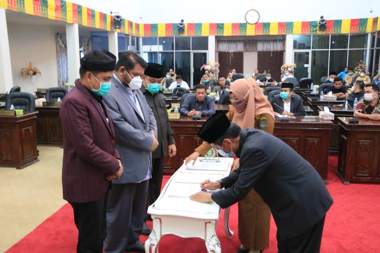 Pjs Bupati Rohul Masrul Kasmy, Ketua DPRD Novliwanda Ade Putra tandatangani berita acara disetujuinya Ranperda tentang RAPBD) menjadi Perda APBD Rohul tahun 2021.