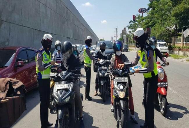 Personel Ditlantas Polda Riau melakukan sosialisasi dan memberikan brosur penerapan keselamatan berlalu lintas. Foto: Riaupos