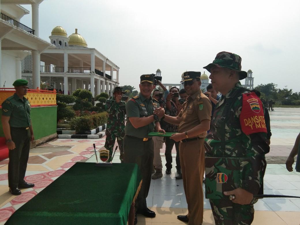 Kasrem 031/Wirabima, Kolonel Inf Asep Nugraha menyerahkan berita acara kepada Bupati Rohil, H Suyatno Amp saat penutupan TMMD ke 105, Ditaman Budaya, belum lama ini.