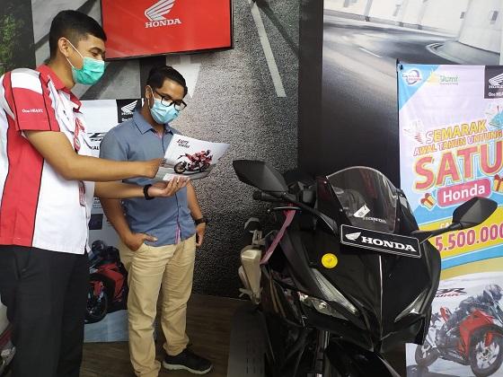 CDNRiau_Petugas Honda sedang memperlihatkan brosur kepada konsumen yang berkunjung ke Showroom