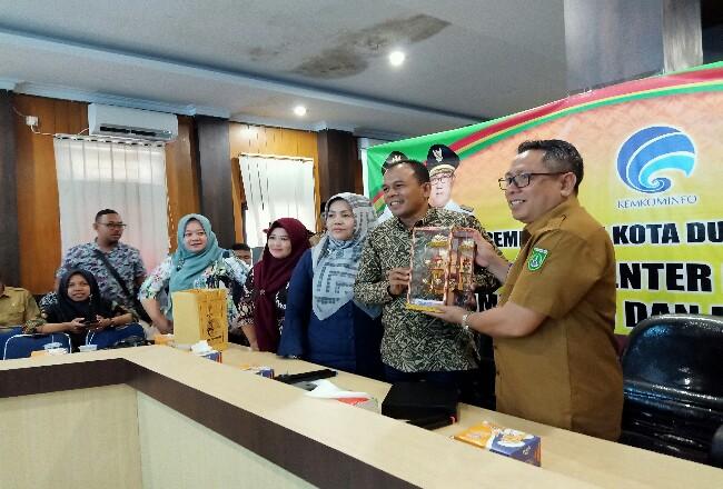 Kadiskominfo Dumai Muhammad Fauzan dan Kadiskominfo Pariaman Hendri saling tukar cinderamata dalam kegiatan studi banding.
