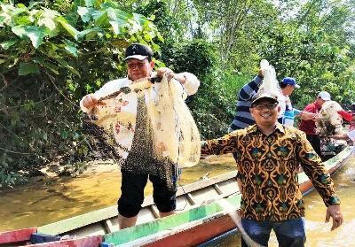 Bupati Sukiman, mengawali menebar jala saat hadiri pembukaan tradisi Rantau Larangan Sei Pusu di Dusun III Kampung Tinggi, Desa Rokan Koto Ruang, Kecamatan Rokan IV Koto.