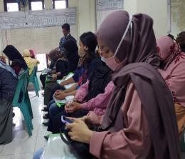 Salah seorang anggota KPPS mencoba aplikasi Si Rekap di android saat kegiatan Bimtek di aula Kantor Lurah Jayamukti, Senin (30/11/2020). Foto IST