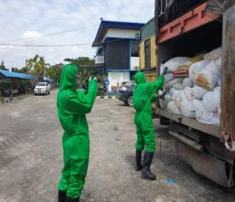 Petugas BC Dumai berpakaian APD lengkap menurunkan limbah Alkes dari truk.