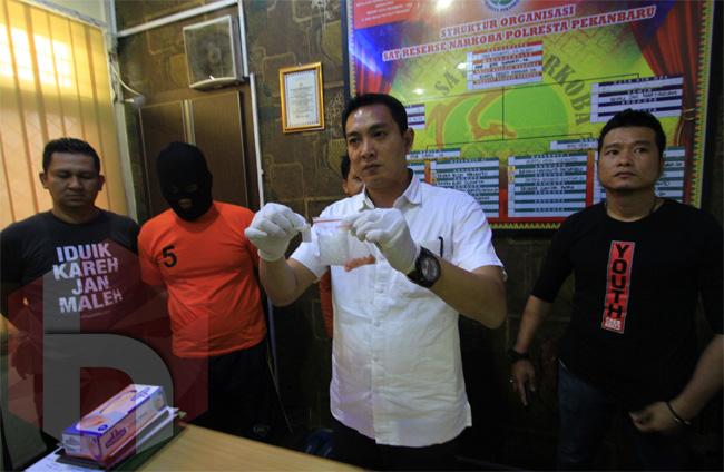Kasat Res Narkoba Polresta Pekanbaru, Kompol Deddi Herman menunjukan barang bukti narkoba bersama dengan tersangka saat gelar ekspos di Mapolresta, Pekanbaru, Riau, Selasa (23/1/2018). Jajaran Polresta Pekanbaru berhasil meringkus oknum Polisi berinisial DAS dan istrinya NS terkait peredaran gelap narkotika jenis setengah ons sabu-sabu dan 24 butir pil ekstasi berbentuk cumi-cumi. <b>FOTO: Wahyudi<br></b><br>